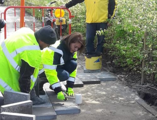 Burgemeester helpt stadsarbeiders een handje bij aanleg voetpad